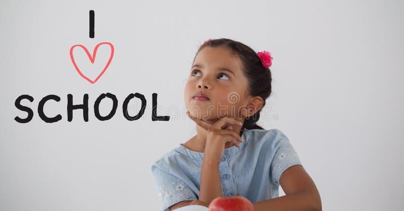 Ragazza dello studente alla tavola che pensa contro il fondo bianco con il testo di scuola di amore di I fotografie stock