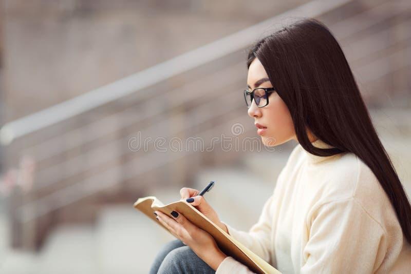 Ragazza dello studente che fa compito in blocco note, sedentesi sulle scale della città immagini stock libere da diritti