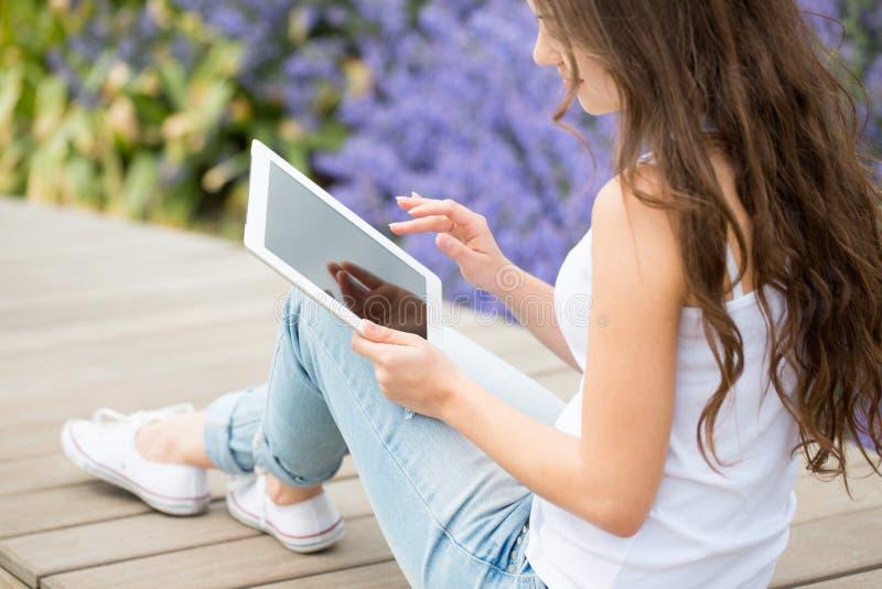 Ragazza dello studente che per mezzo del computer della compressa immagini stock libere da diritti