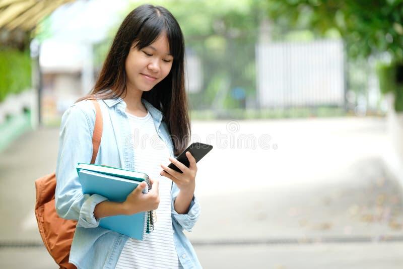 Ragazza dello studente che tiene i libri e che per mezzo dello smartphone, istruzione online, comunicazione di tecnologia immagine stock