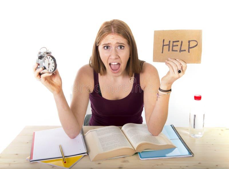 Ragazza dello studente di college nello sforzo che chiede il concetto dell'esame di tempo della sveglia della tenuta di aiuto fotografie stock