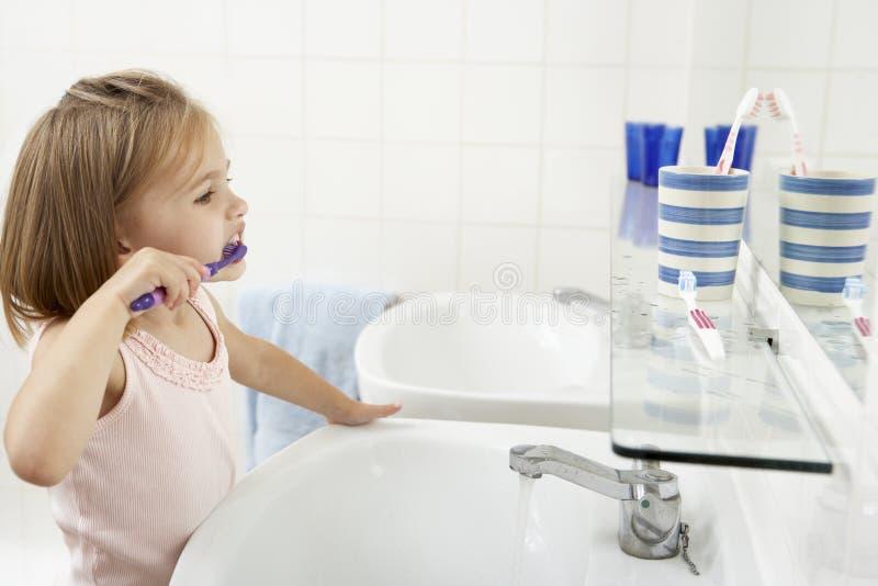 Ragazza in denti di spazzolatura del bagno immagini stock libere da diritti
