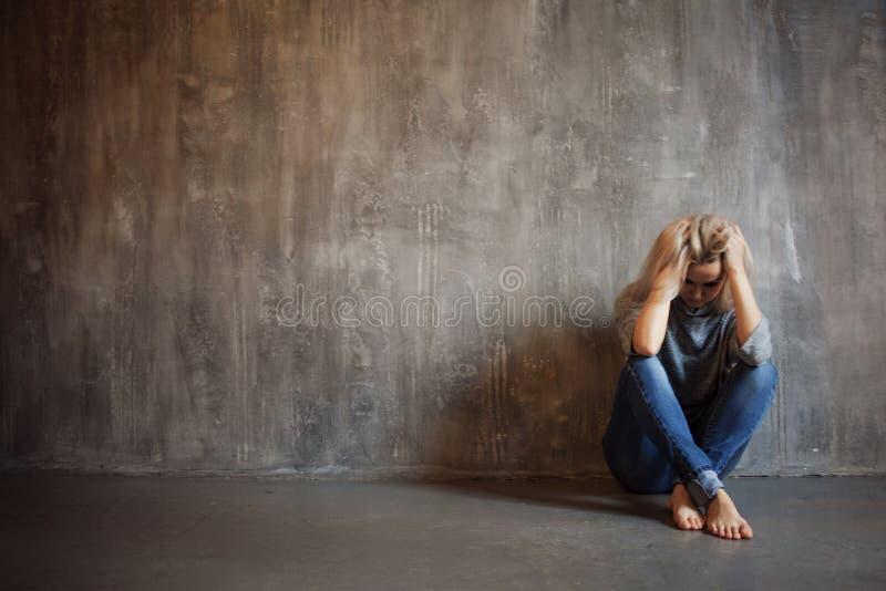 Ragazza deprimente Giovane bella bionda in maglione grigio e jeans fotografie stock