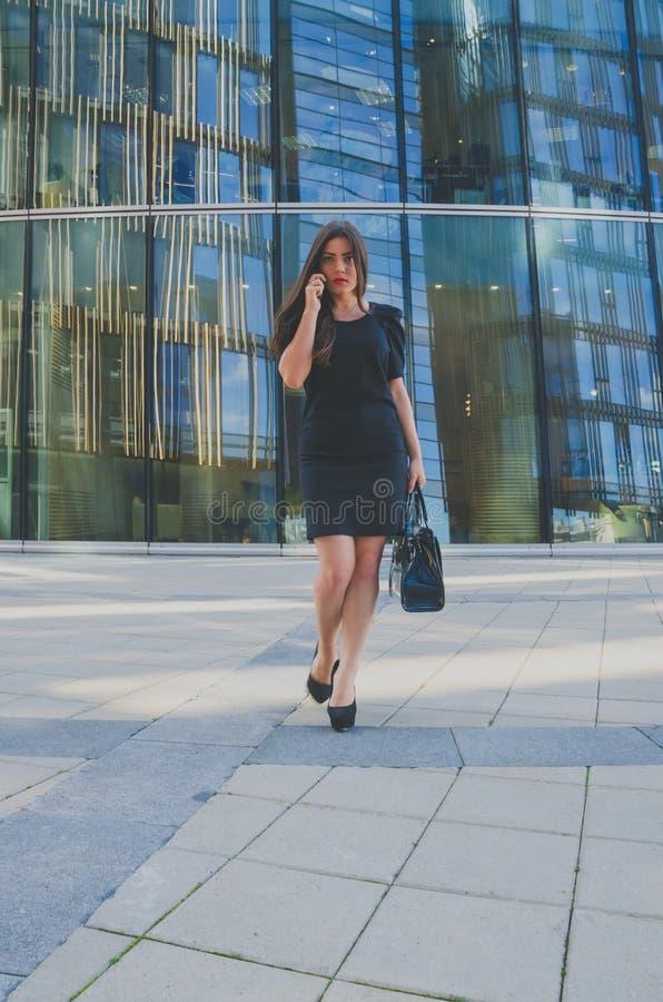 Ragazza di affari in un vestito nero che parla sul telefono nella borsa immagini stock libere da diritti