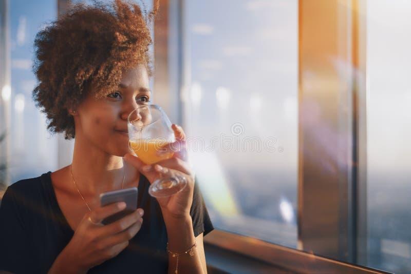 Ragazza di afro con vetro del juica e dello smartphone fotografia stock libera da diritti