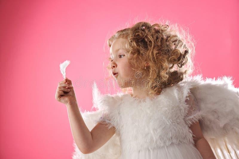 Ragazza di angelo che tiene una piuma fotografia stock libera da diritti