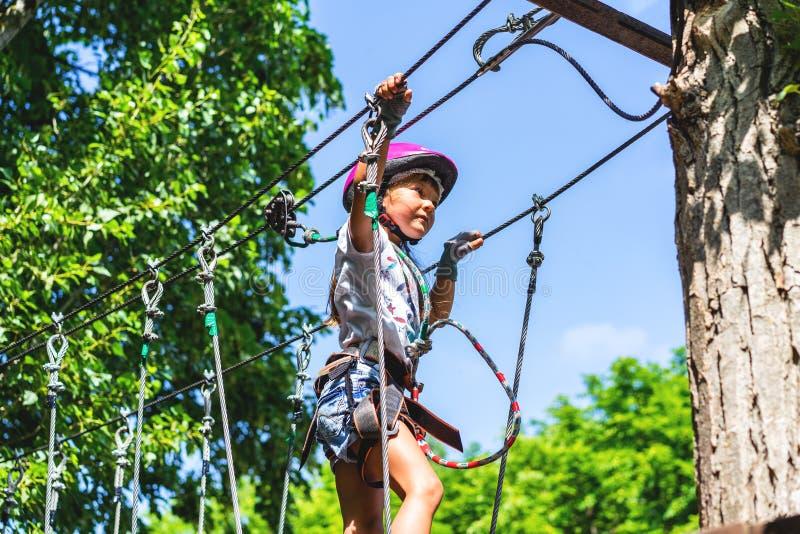 Ragazza di 5 anni felice in casco protettivo rosa ed attrezzatura in un parco della corda di estate immagini stock