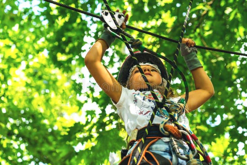 Ragazza di 5 anni felice in casco protettivo rosa ed attrezzatura in un parco della corda di estate fotografia stock