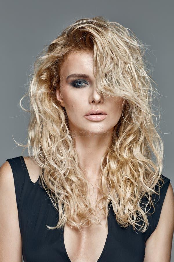 Ragazza di Beautifu con capelli biondi ricci lunghi fotografia stock libera da diritti