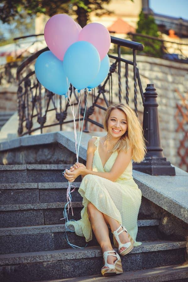 Ragazza di bellezza con i palloni variopinti che ride sui punti della città Bella giovane donna felice un giorno luminoso soleggi fotografia stock