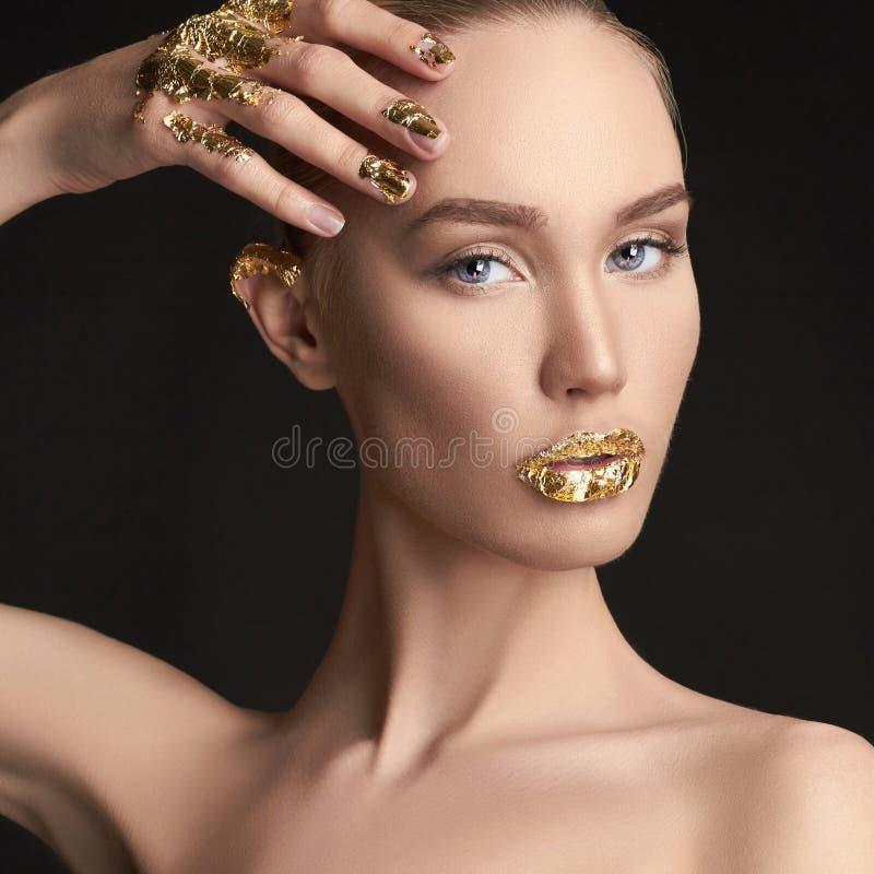 Ragazza di bellezza con trucco dorato immagine stock