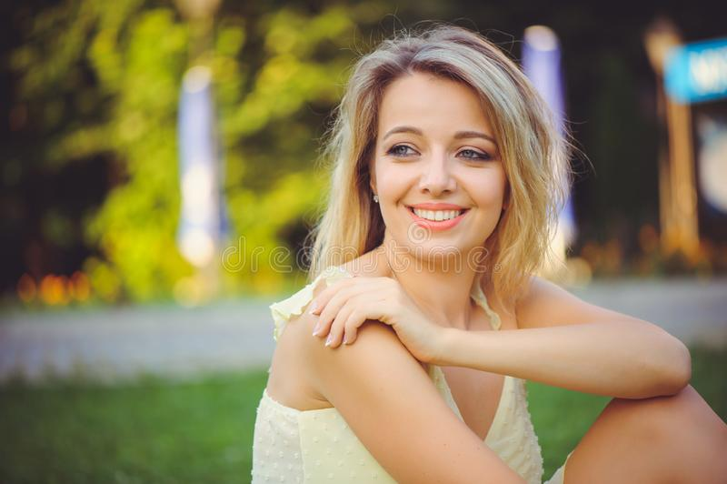 Ragazza di bellezza con un sorriso romantico delicato sui precedenti del parco di estate Bella giovane donna felice che riposa, c fotografie stock