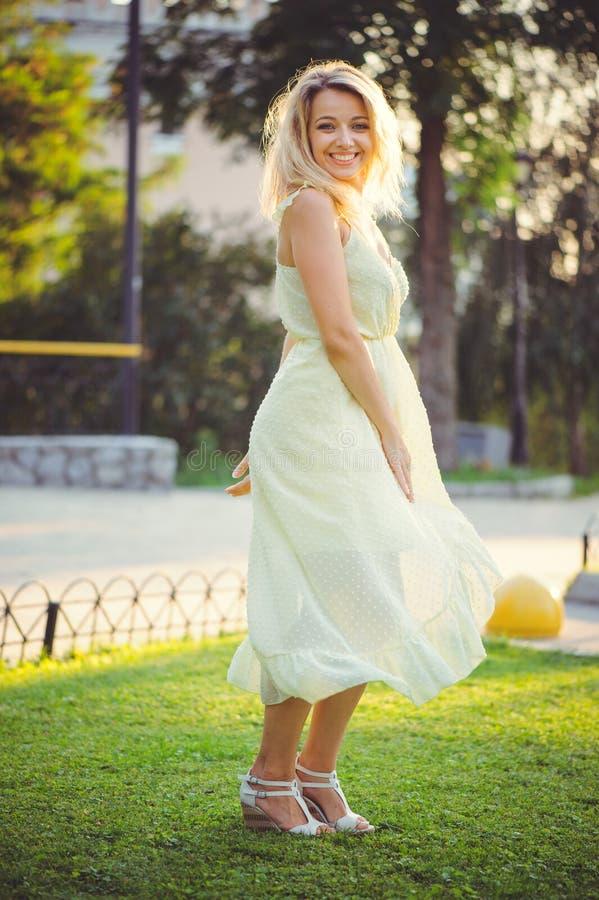 Ragazza di bellezza con un sorriso romantico delicato sui precedenti del parco di estate Bella giovane donna felice che riposa, c immagine stock