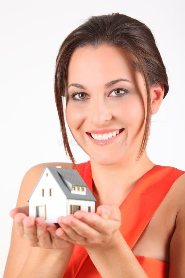 Ragazza di bellezza in vestito rosso con il modello della casa fotografia stock libera da diritti