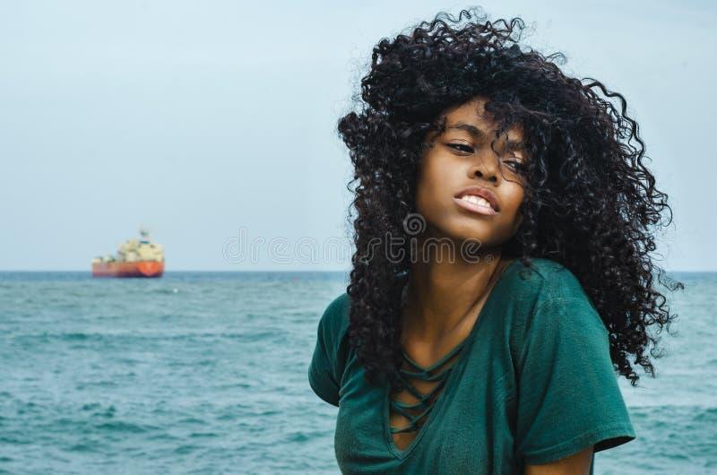 Ragazza di colore nero, capelli di risata in ruota di ferris, sedentesi godendo di un giorno di estate fotografia stock