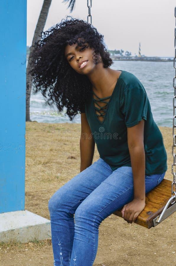 Ragazza di colore nero, capelli di risata in ruota di ferris, sedentesi godendo di un giorno di estate immagini stock