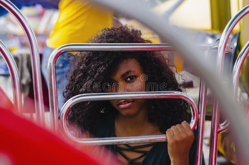 Ragazza di colore nero, capelli di risata in ruota di ferris, sedentesi godendo di un giorno di estate immagine stock