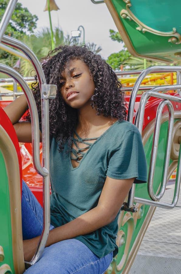 Ragazza di colore nero, capelli di risata in ruota di ferris, sedentesi godendo di un giorno di estate fotografia stock libera da diritti