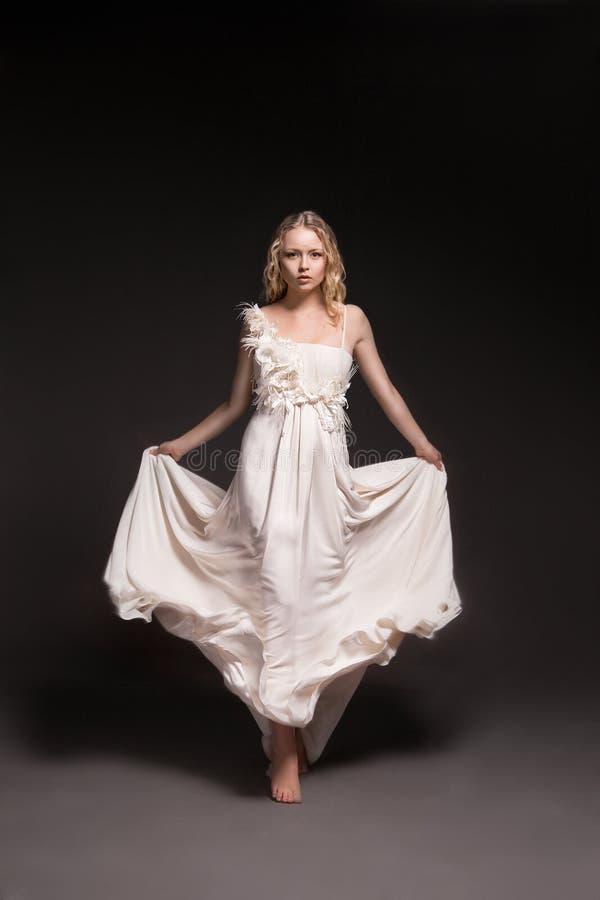 Ragazza di dancing in vestito da sposa sopra fondo scuro immagine stock