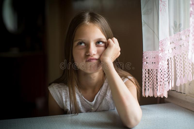 Ragazza di dieci anni divertente sveglia che si siede alla tavola proposta fotografie stock