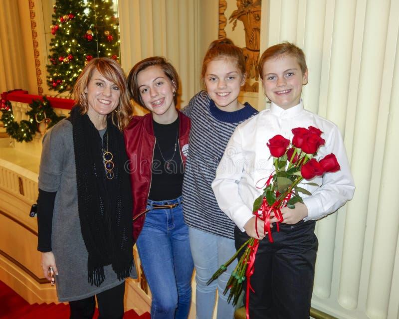 Ragazza di dieci anni sorridente che sta sulle scala rosse con la madre e le sorelle di mezza età fotografia stock