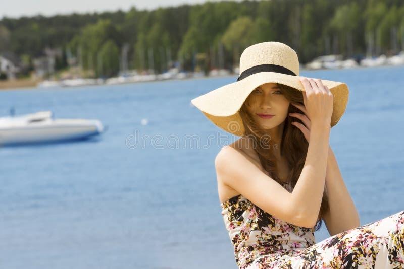 Ragazza di estate con il cappello vicino al lago Colore d'annata immagine stock