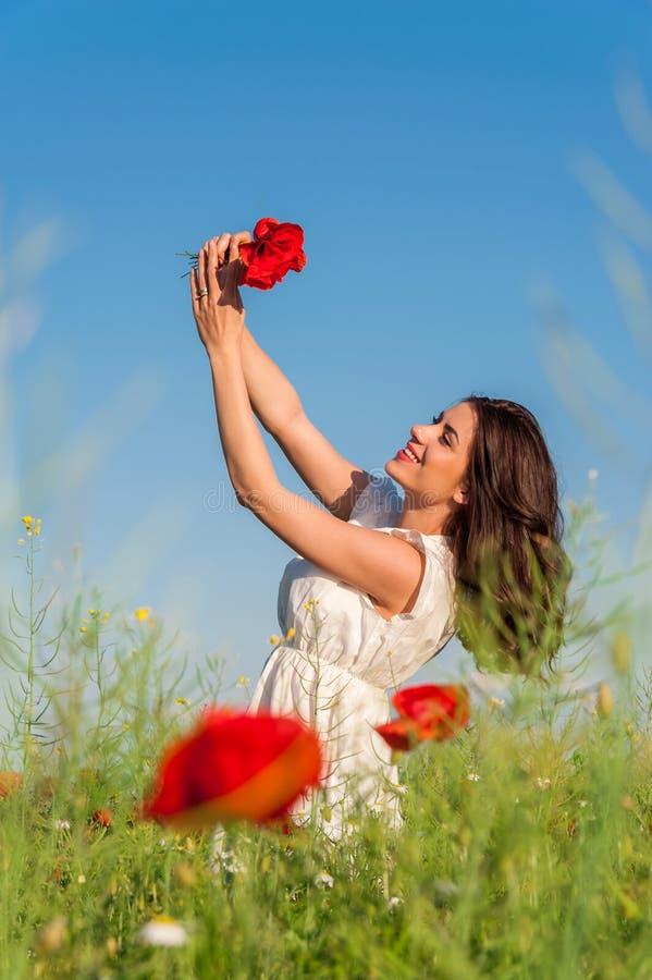 Ragazza di estate nel campo del papavero che tiene un mazzo dei papaveri fotografia stock