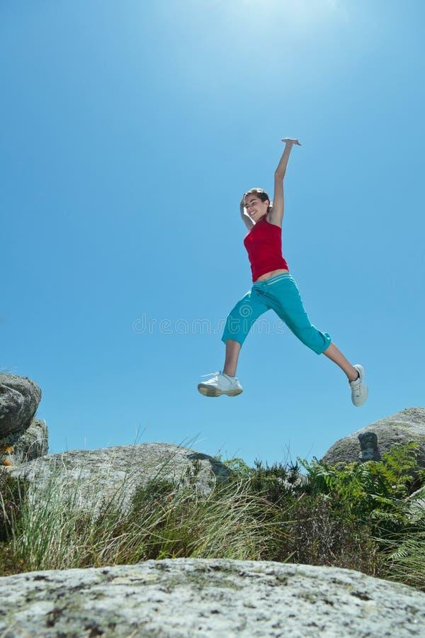 Ragazza di forma fisica che salta sopra le rocce fotografie stock libere da diritti