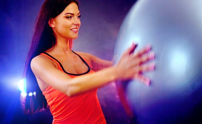 Ragazza di forma fisica che si esercita nella palestra con fitball immagine stock