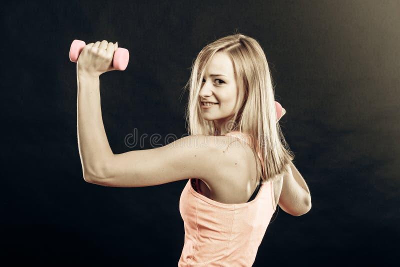 Ragazza di forma fisica con le teste di legno che flettono i muscoli in palestra fotografia stock libera da diritti