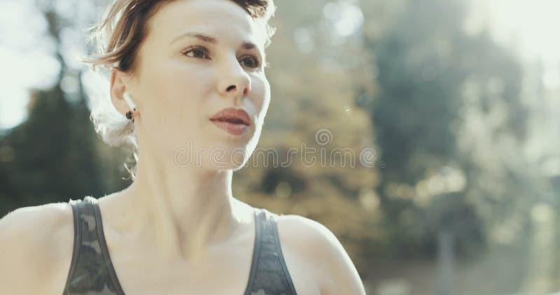 Ragazza di forma fisica del primo piano che mette in cuffie senza fili dell'orecchio Airpods d'uso del corridore della donna dell fotografie stock libere da diritti