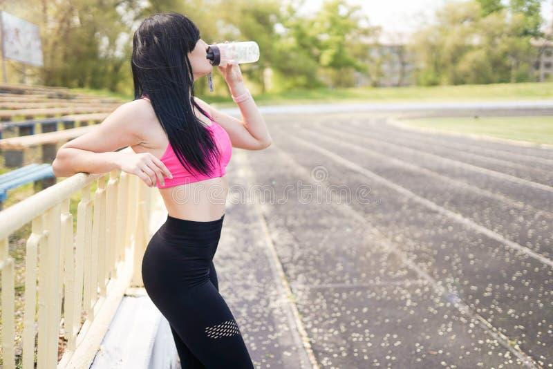 Ragazza di forma fisica Fondo di sport con lo spazio della copia Giovane bella donna in acqua potabile degli abiti sportivi Conce fotografie stock