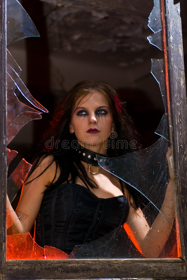 Ragazza di Goth in finestra fotografie stock