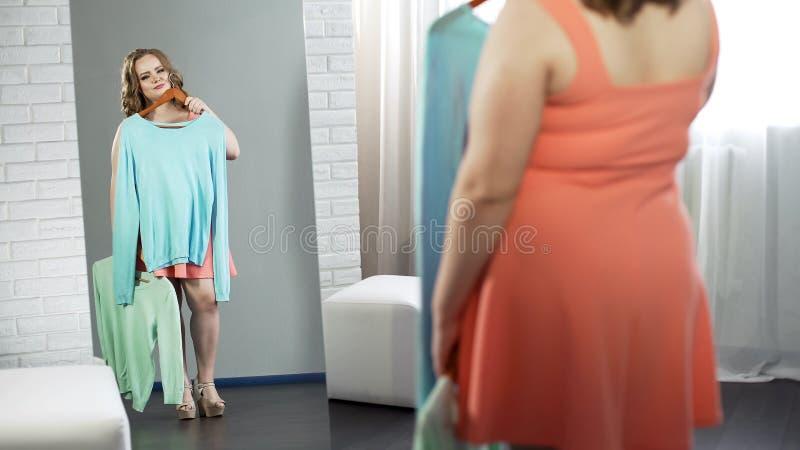 Ragazza di grande misura sicura che sceglie blusa nello spogliatoio, più modo di dimensione immagine stock