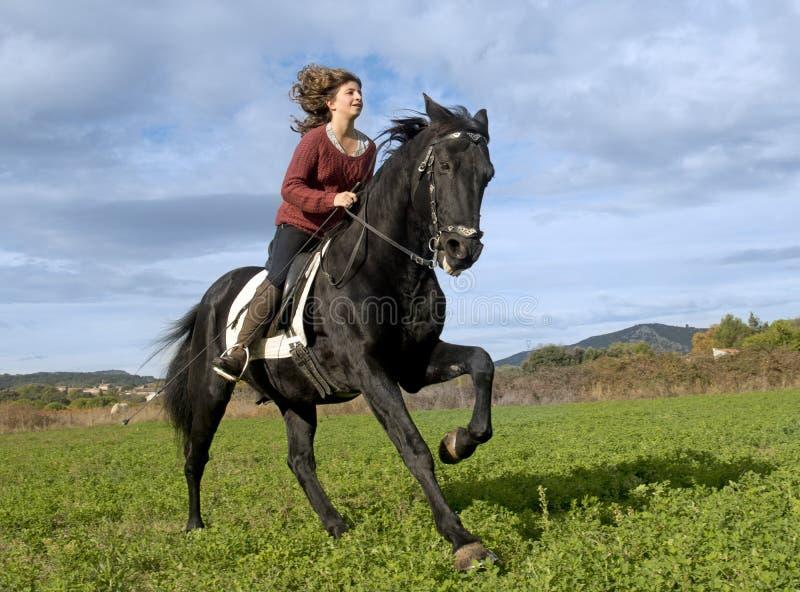 Ragazza di guida e stallone nero fotografie stock libere da diritti