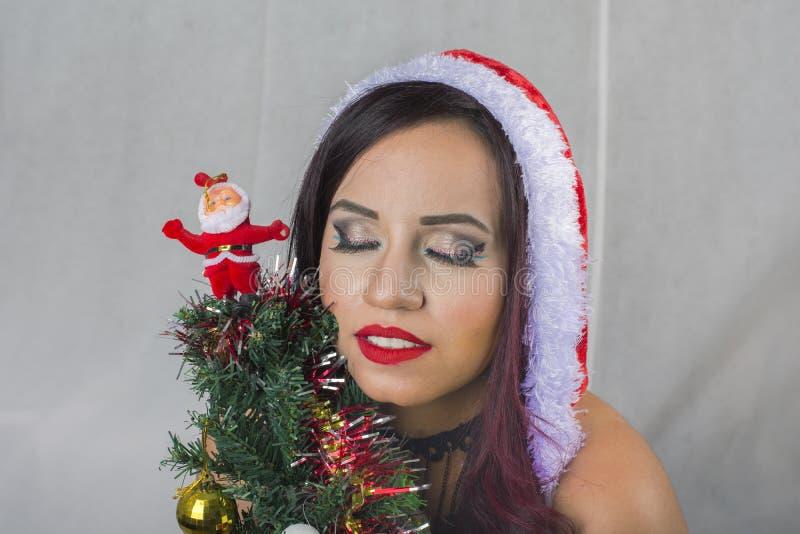Ragazza di inverno che indossa l'albero della tenuta del costume di Santa Claus fotografia stock