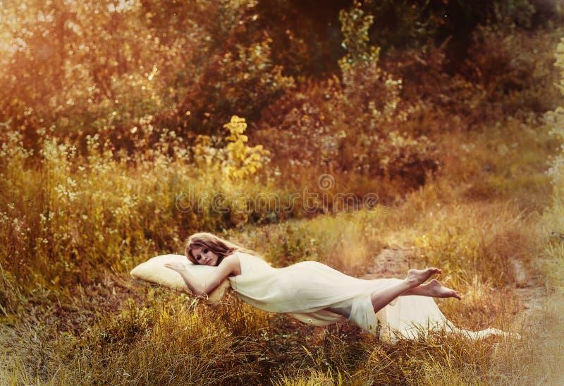 Ragazza di levitazione sul cuscino Sogno dolce delle ragazze di sogno del volo fotografie stock libere da diritti
