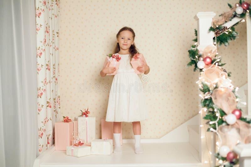 Ragazza di Littile in vestito con i regali di natale immagine stock