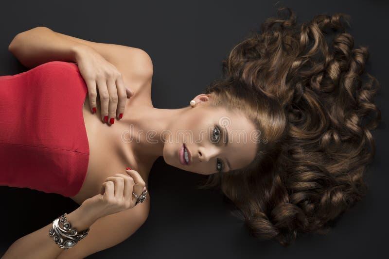 Ragazza di menzogne sexy con capelli ricci e la mano lunghi sul torace fotografie stock
