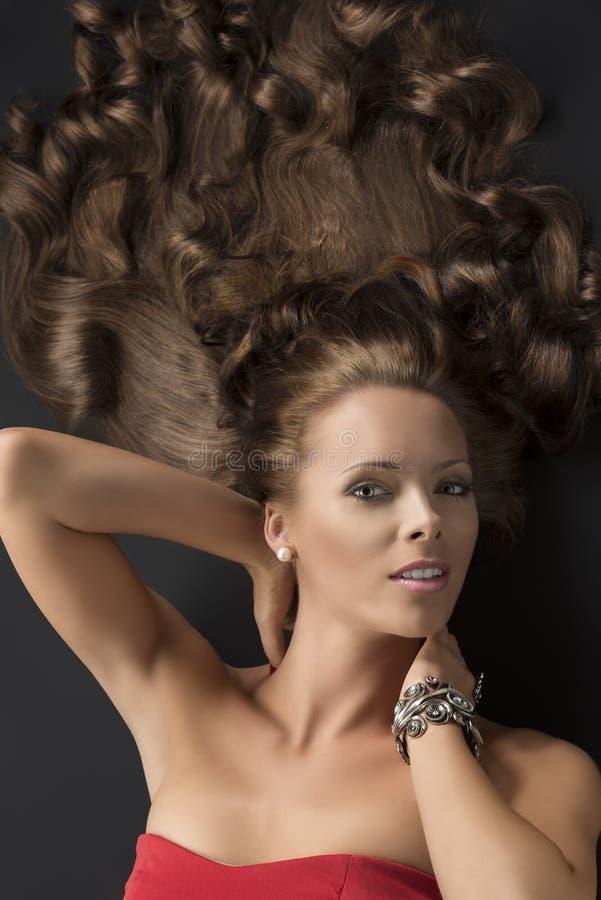 Ragazza di menzogne sexy con capelli ricci lunghi ed entrambe le mani sul collo fotografia stock libera da diritti
