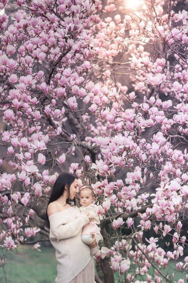 Ragazza di 6 mesi del bambino sveglio in attrezzatura rosa con gli occhi di Big Blue con la giovane bella madre alla primavera, a fotografia stock libera da diritti