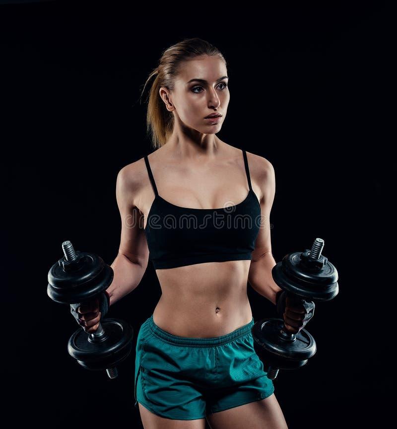 Ragazza di modello atletica sveglia in abiti sportivi con le teste di legno in studio contro fondo nero Figura femminile ideale d fotografia stock