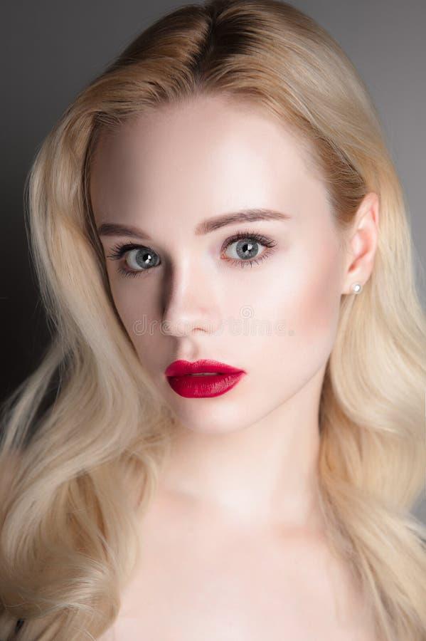Ragazza di modello di bellezza con le labbra rosse e gli occhi azzurri di trucco perfetto che esaminano macchina fotografica Ritr immagine stock libera da diritti