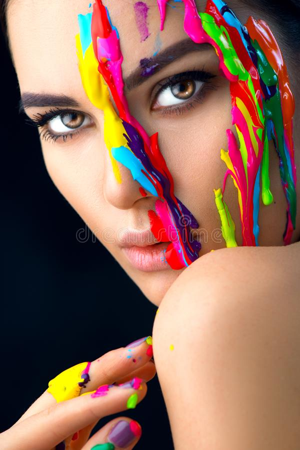 Ragazza di modello di bellezza con pittura variopinta sul suo fronte Ritratto di bella donna con la pittura del liquido corrente immagini stock