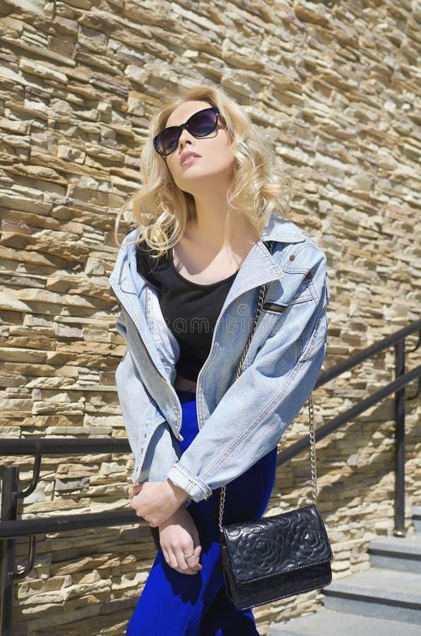 Ragazza di modello bionda alla moda con la borsa fotografie stock libere da diritti