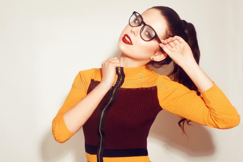 Ragazza di modello castana di modo di bellezza che indossa i vetri alla moda Donna sexy con trucco perfetto, il vestito arancio e fotografia stock libera da diritti