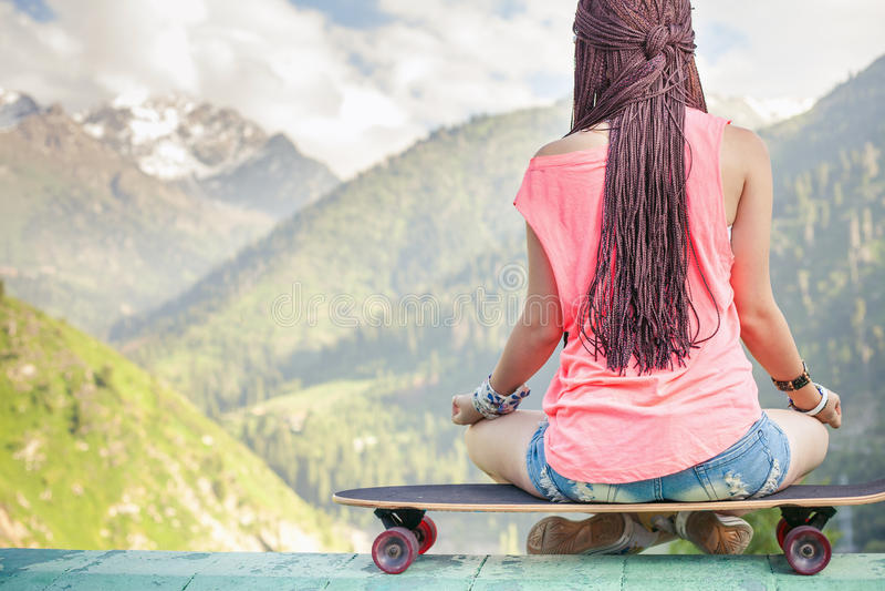 Ragazza di modo dei pantaloni a vita bassa che fa yoga, rilassantesi sul pattino alla montagna immagine stock