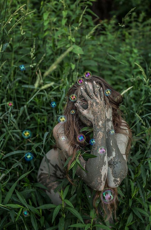 Ragazza di Muddy Amazon che si nasconde dietro un cespuglio nel legno, mentre bolle di sapone che volano intorno lei fotografia stock libera da diritti