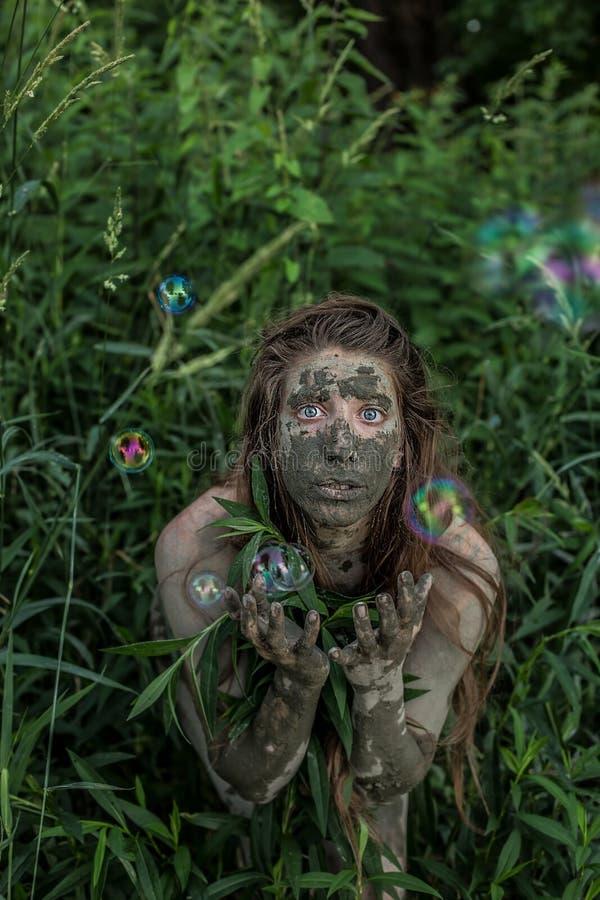 Ragazza di Muddy Amazon che si nasconde dietro un cespuglio nel legno, mentre bolle di sapone che volano intorno lei immagini stock libere da diritti