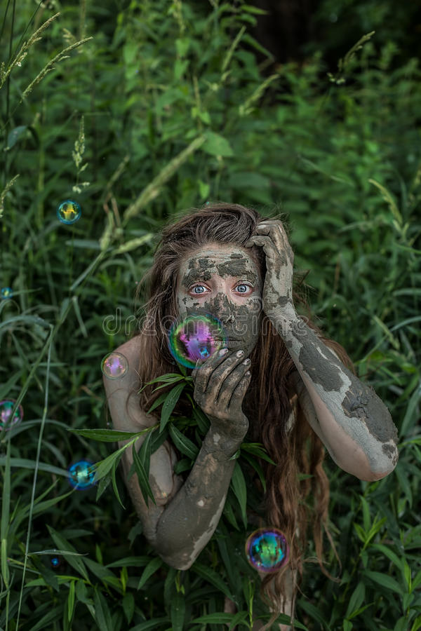 Ragazza di Muddy Amazon che si nasconde dietro un cespuglio nel legno, mentre bolle di sapone che volano intorno lei fotografia stock